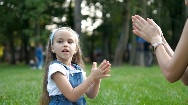 Menina bonita criança jogando jogo com a mãe com as mãos ao ar livre no parque verde de verão.