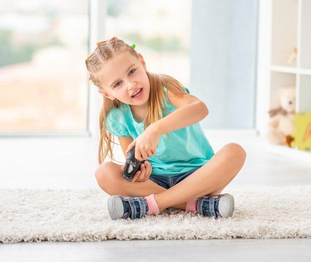 Menina bonita criança jogando videogame no console