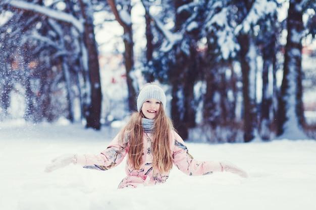 Menina bonita criança na floresta de inverno