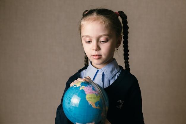 Menina bonita criança olha o globo