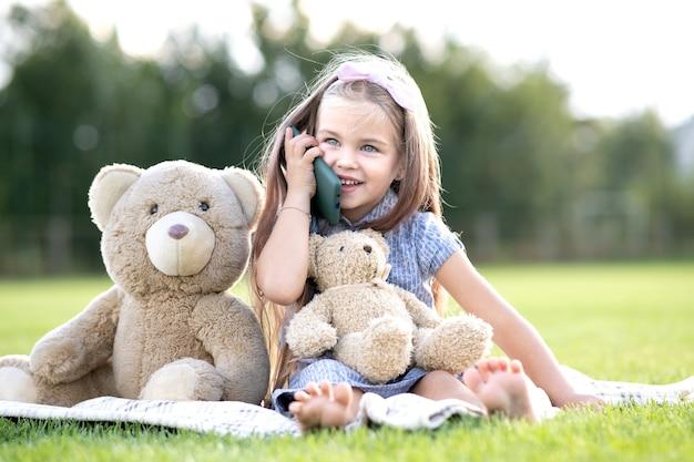 Menina bonita criança sentada no parque de verão junto com seu ursinho de pelúcia brinquedo falando no celular, sorrindo alegremente ao ar livre no verão.