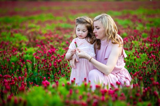 Menina bonita criança sorridente com a jovem mãe em família olhar no campo de flores de trevo em vez por do sol