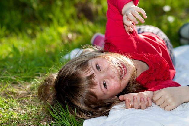 Menina bonita criança sorridente com olhos cinzentos e cabelos louros longos se divertindo ao ar livre, deitado na grama verde no campo ensolarado verde verão turva. beleza, sonhos e jogos de infância.