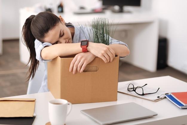 Menina bonita cruzando os braços, mantendo os olhos fechados, enquanto está sentada no local de trabalho