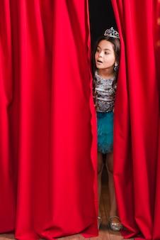 Menina bonita curiosa a espreitar da cortina vermelha no palco