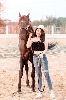 Menina bonita da ásia cuidando de seu cavalo com amor e carinho.