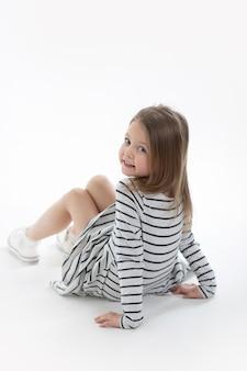 Menina bonita da criança com um sorriso bonito travesso está sentada sobre um fundo branco e olhando para a câmera. copie o espaço para texto, mock up, banner