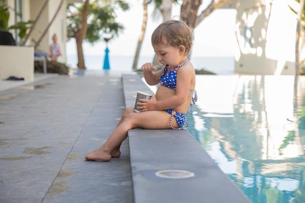 Menina bonita da criança em traje de banho, comendo iogurte sentado à beira da piscina. close up, foco suave
