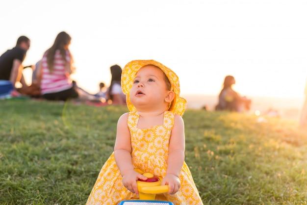Menina bonita da criança pequena que senta-se em um carro do brinquedo fora.