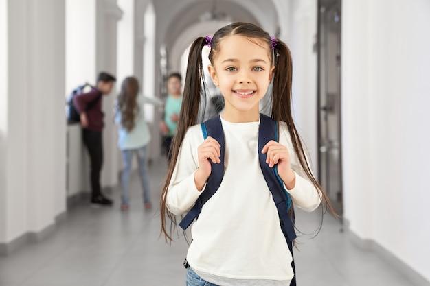 Menina bonita da escola morena sorrindo feliz