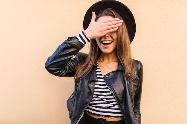 Menina bonita da moda em jaqueta de couro e chapéu preto cobrindo os olhos do rosto com a mão isolada na parede amarela clara