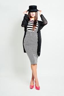 Menina bonita da moda usando o chapéu do moderno. foto do estúdio de beleza da moda