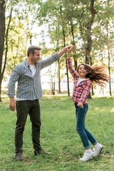 Menina bonita dançando com o pai na terra gramada no parque