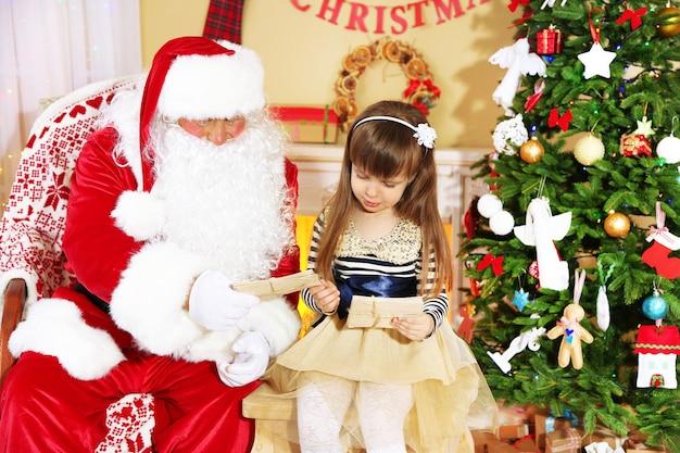 Menina bonita dando cartas com desejos para o papai noel perto da árvore de natal em casa