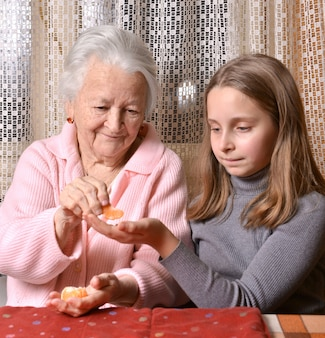 Menina bonita dando laranjas mandarim para a avó dele