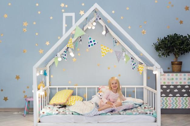 Menina bonita de 3 anos sentada na cama de casa bonita