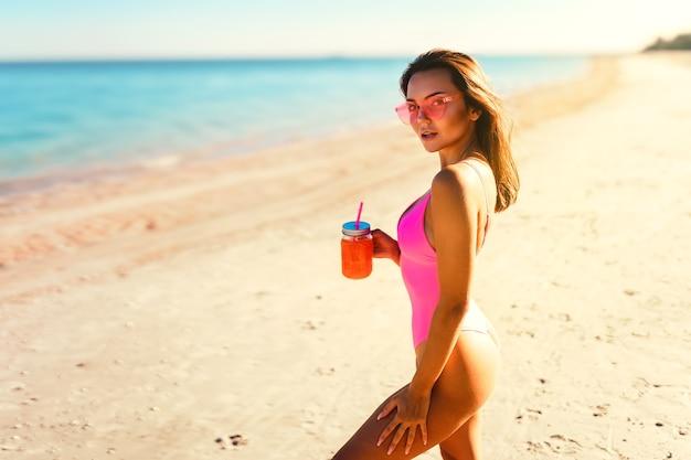 Menina bonita de biquíni em seu corpo perfeito caminhando pela areia branca do mar enquanto dá um coquetel de férias