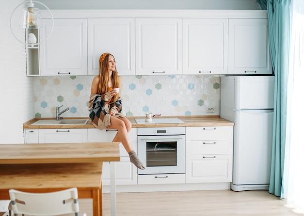 Menina bonita de cabelo comprido justo jovem sorridente, vestindo casaco de malha aconchegante com xícara de café da manhã, sentado na superfície de trabalho de cozinha em casa