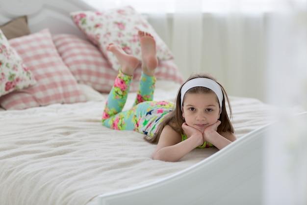 Menina bonita de cabelo escuro doce de pijama deita na cama