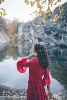 Menina bonita de cabelos cacheados em um vestido vermelho olhando para o lago