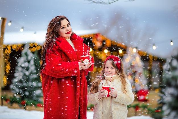 Menina bonita de cabelos compridos e mulher morena bonita posando com canecas de natal na pista de patinação aberta. fundo de natal.