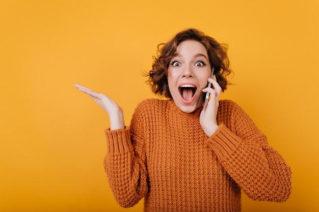 Menina bonita de cabelos curtos com expressão facial animada falando ao telefone