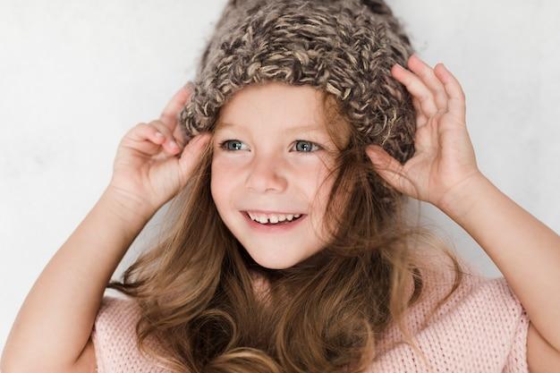 Menina bonita de close-up com chapéu de inverno