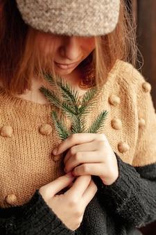 Menina bonita de close-up com galho de árvore do abeto