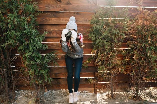 Menina bonita de corpo inteiro com cabelo comprido no chapéu de malha, luvas e jeans tirando foto na câmera em madeira surround ramos verdes.