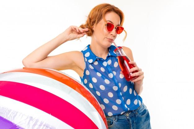 Menina bonita de óculos de sol segura uma bola grande inflável para nadar e um copo de vidro com um canudo em branco