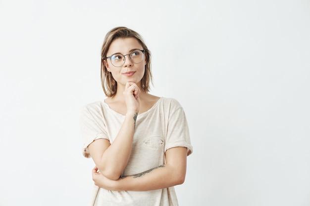 Menina bonita de óculos pensando olhando de lado.
