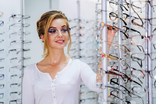 Menina bonita de óculos perto do stand na loja de óptica