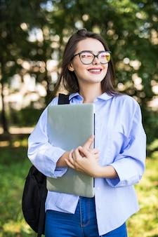 Menina bonita de óculos transparentes fica com seu laptop no parque