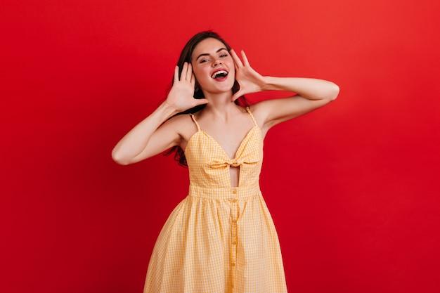 Menina bonita de ótimo humor grita bem alto. retrato de senhora com batom vermelho em vestido de verão xadrez na parede brilhante isolada.