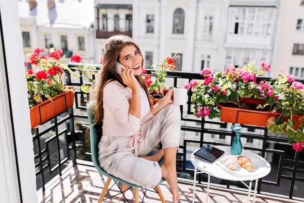 Menina bonita de pijama, tomando café da manhã na varanda da manhã ensolarada. ela segura uma xícara, falando no telefone sorrindo.