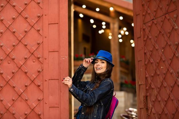 Menina bonita de sorriso no chapéu azul perto do edifício velho com as portas vermelhas antigas. modelo feminino posando