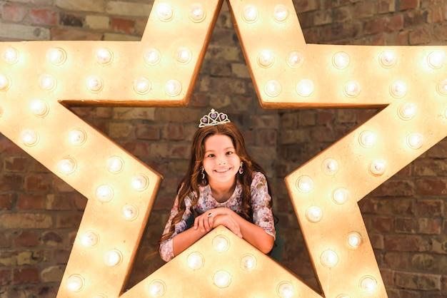 Menina bonita de sorriso que veste a inclinação na estrela de incandescência contra a parede de tijolo
