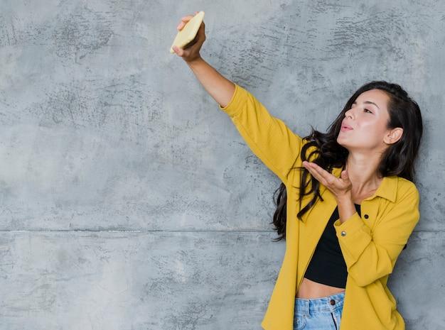 Menina bonita de tiro médio tomando uma selfie