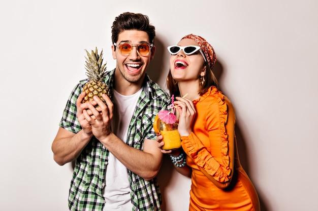 Menina bonita de vestido laranja e cara de camisa verde e óculos escuros estão rindo e posando com abacaxi e coquetel.