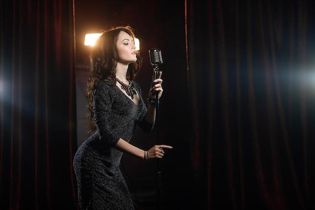 Menina bonita de vestido preto, cantando no microfone na sala de concertos