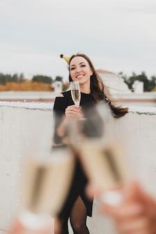 Menina bonita de vestido preto no fundo de animar copos de champanhe