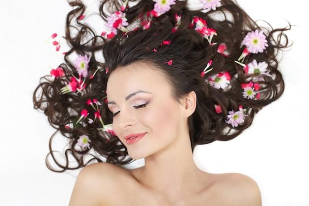 Menina bonita, deitado com flores vermelhas brilhantes em sua maquiagem brilhante cabelo isolada no branco