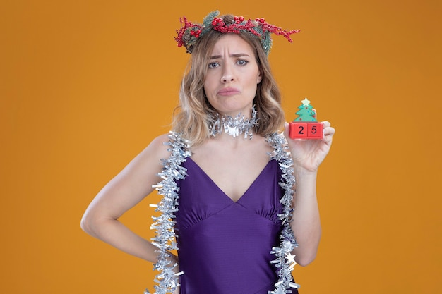 Menina bonita desagradável com vestido roxo e grinalda com guirlanda no pescoço segurando um brinquedo de natal e colocando a mão no quadril isolado no fundo marrom