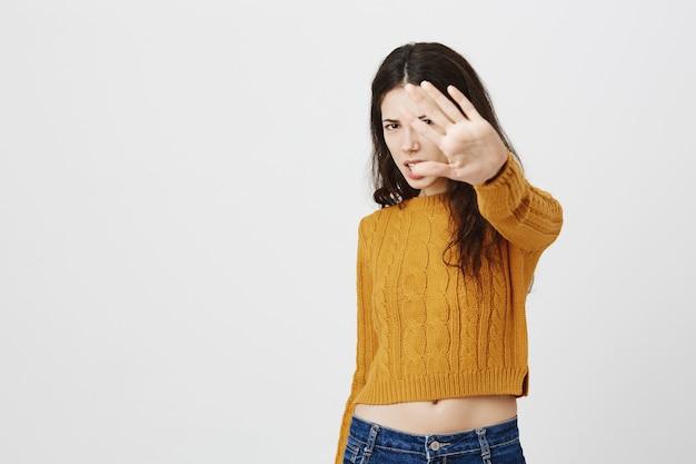 Menina bonita descontente e incomodada estende a mão para rejeitar ou parar de fotografar, não gosta de tirar fotos de si mesma