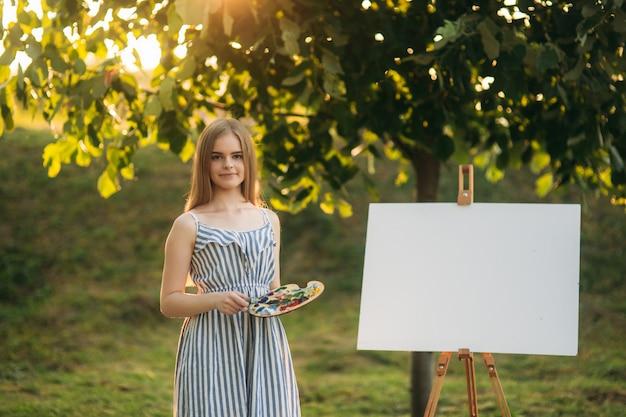 Menina bonita desenha uma imagem no parque usando uma paleta com tintas e uma espátula. cavalete e tela com uma foto.