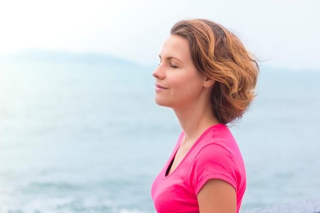Menina bonita, desfrutando de andar no clima ensolarado de bom verão. jovem mulher respirando profundamente, profundamente o ar do mar, sorrindo com os olhos fechados. a vida é boa. senhora relaxada sonhando. calma, conceito de meditação