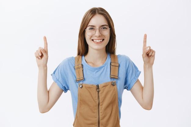 Menina bonita divertida e interessada de óculos apontando o dedo para uma boa oferta promocional
