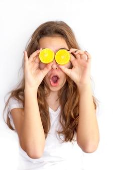 Menina bonita do adolescente que cobre seus olhos com os limões cortados. óculos de sol de limão