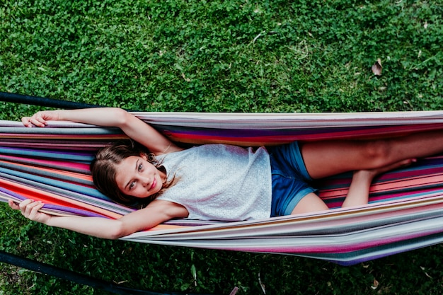 Menina bonita do adolescente que encontra-se na rede colorida no jardim. e sorrindo. relaxar e se divertir ao ar livre