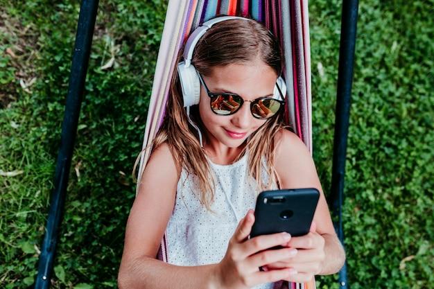 Menina bonita do adolescente que encontra-se na rede colorida no jardim. ouvindo música no celular e fone de ouvido e sorrindo. relaxar e se divertir ao ar livre